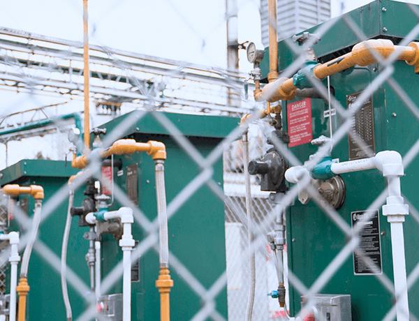 tres generadores color verde frente a una reja de malla blanca
