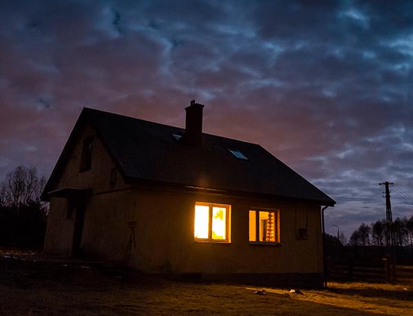 Una casa en medio de la nada con una luz amarilla encendida en su interior