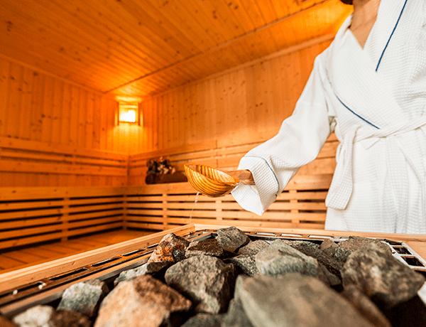 Un hombre riega agua con una cuchara de palo en un cuarto de madera